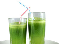 Green vegetable juice in the glasses with straws